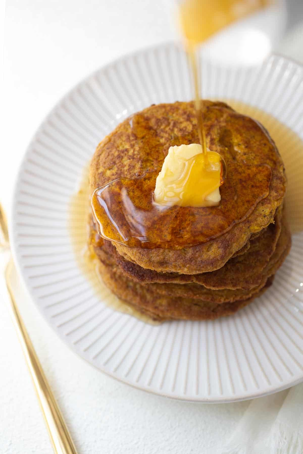 healthy pumpkin pancakes on plate with maple syrup