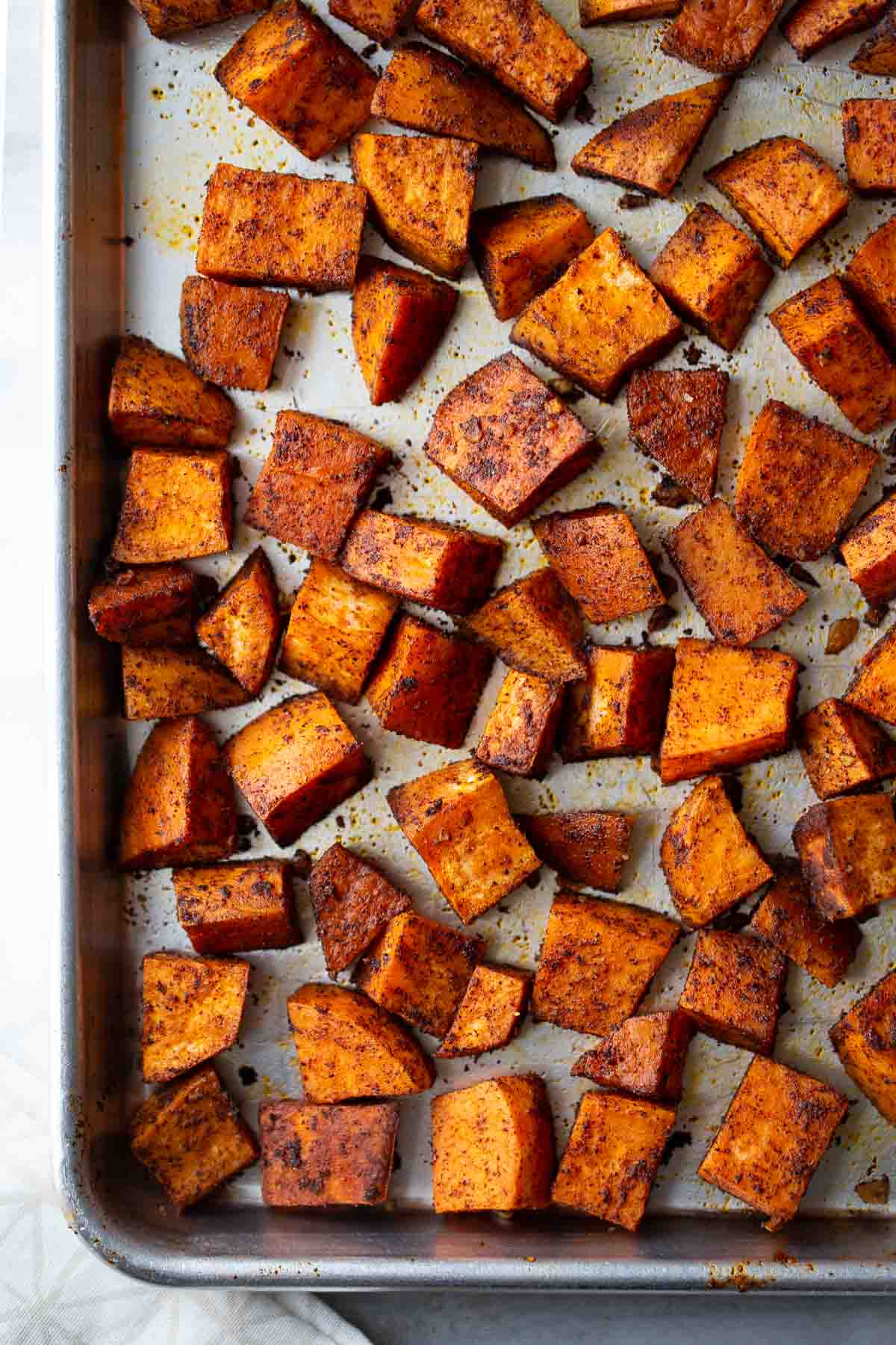 Roasted Sweet Potatoes cubes seasoned with chili powder on pan