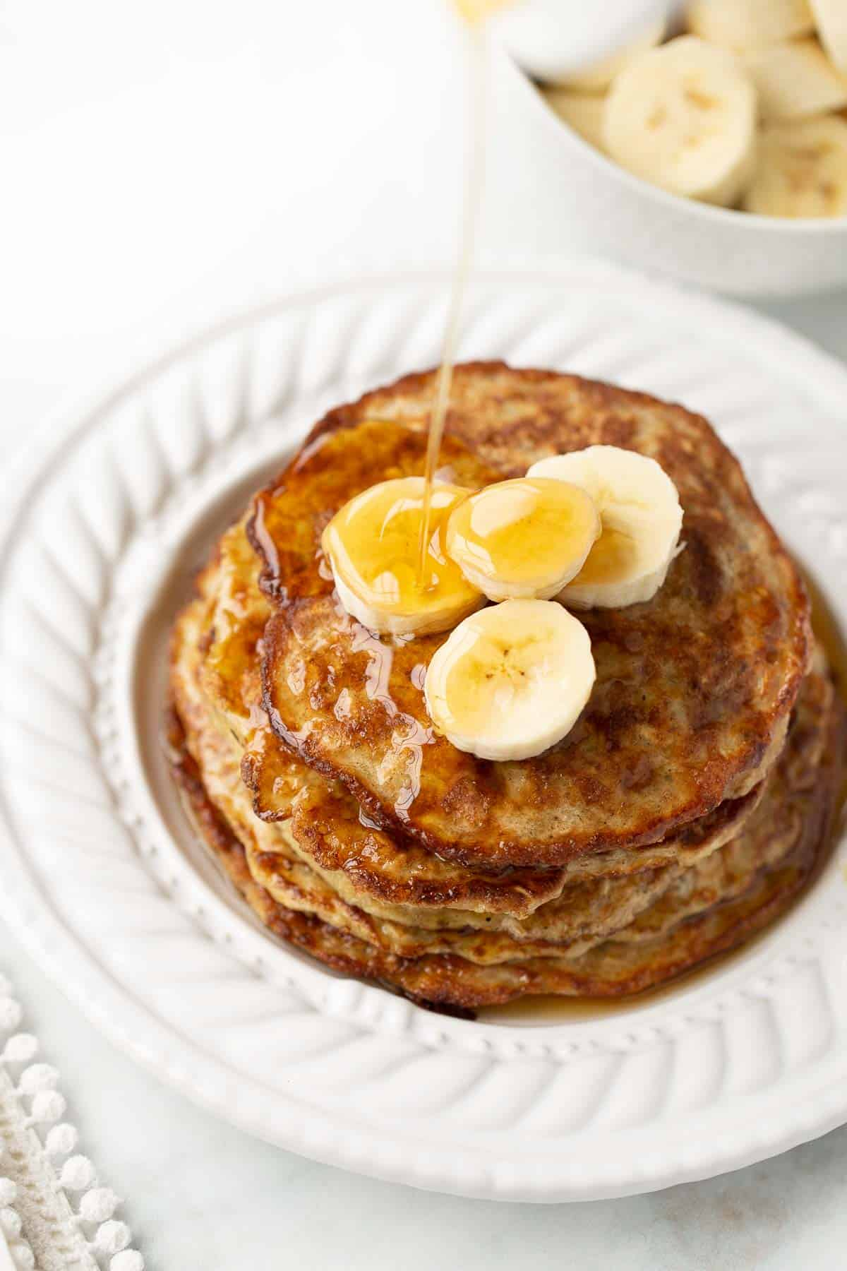 syrup being poured on banana pancakes